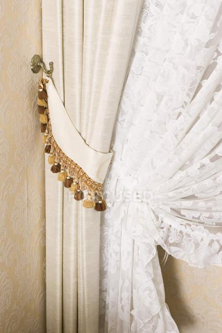 Imagem recortada de cortinas ornamentadas desenhadas de volta — Fotografia de Stock
