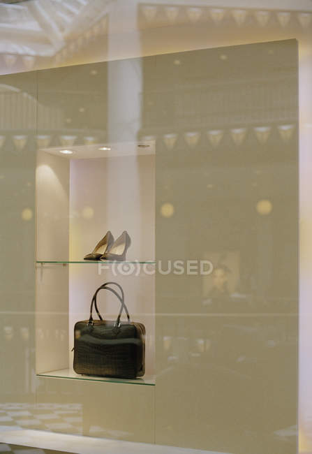 Pair of shoes and handbag in shop window display — Stock Photo