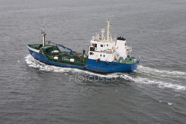 Fishing trawler sailing at rippled sea — Stock Photo