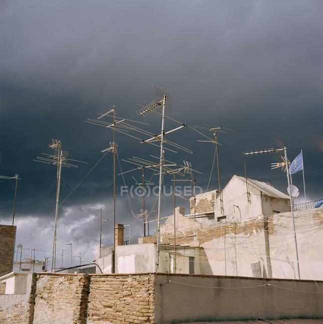 Antenne TV multiple contro un cielo nuvoloso coperto — Foto stock