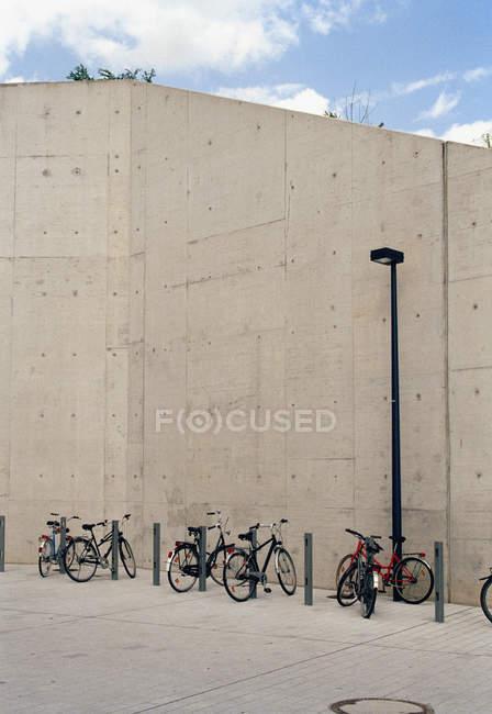 Bicicletas estacionadas ao lado da parede de concreto — Fotografia de Stock