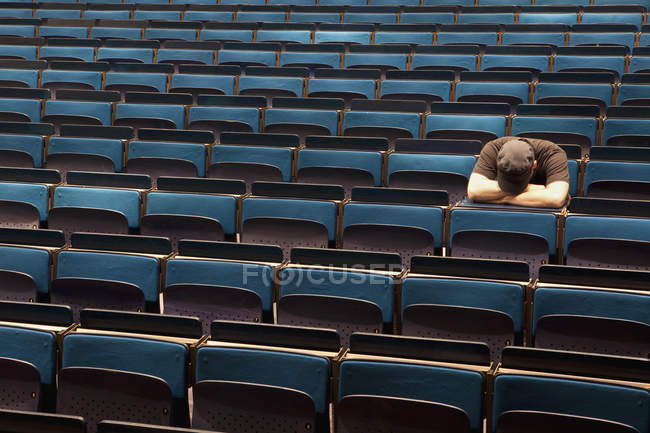 A man sitting in auditorium with head on arms — Stock Photo