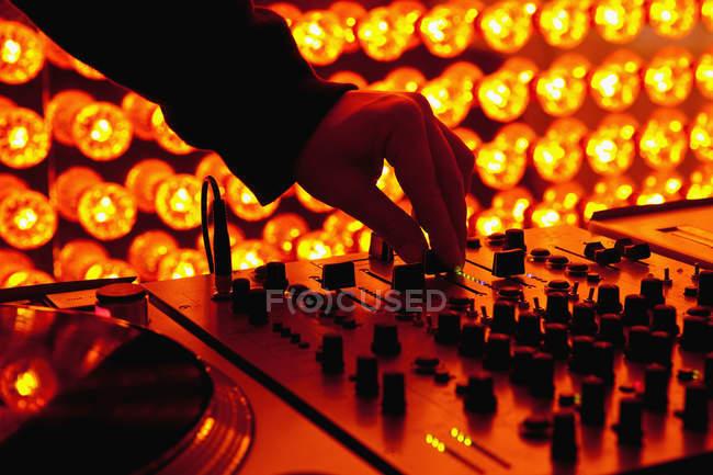 Crop DJ mano di regolazione dei livelli sul mixer del suono in discoteca — Foto stock