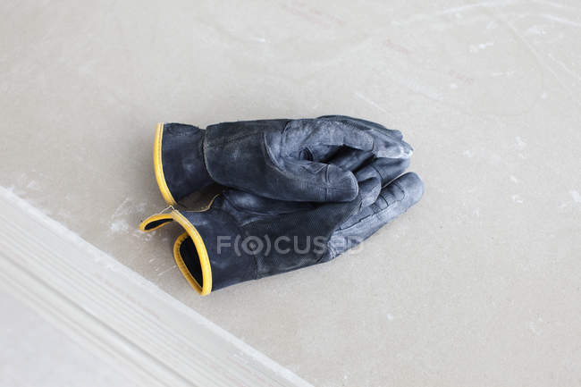 Clasped work gloves on beige surface — Stock Photo
