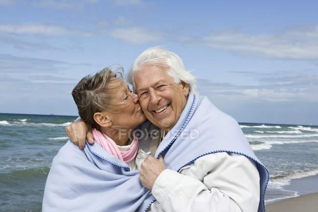Beijos casal sênior caminhando juntos em uma praia — Fotografia de Stock