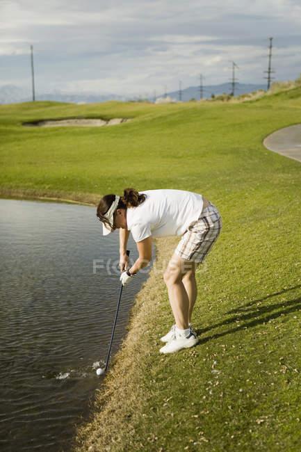 Un golfeur collecte une balle de golf d'un piège à eau — Photo de stock