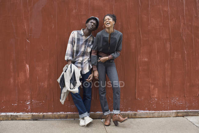Young couple leaning against brown wall outdoors — Stock Photo