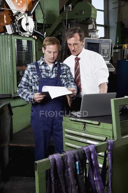 Werksleiter und ein Fabrikarbeiter in einer Metallteilefabrik — Stockfoto