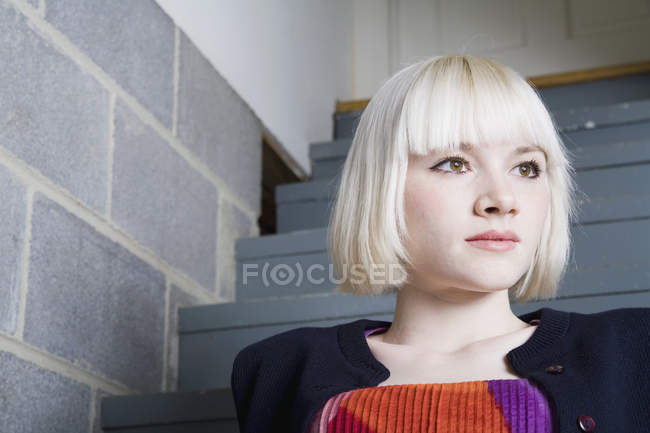 A young woman sitting on steps — Stock Photo