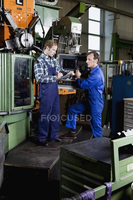 Zwei Männer in einer Metallteilefabrik bei der Überprüfung eines Klemmbretts — Stockfoto