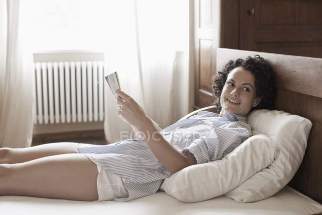 Woman lying down and reading in bed — Stock Photo