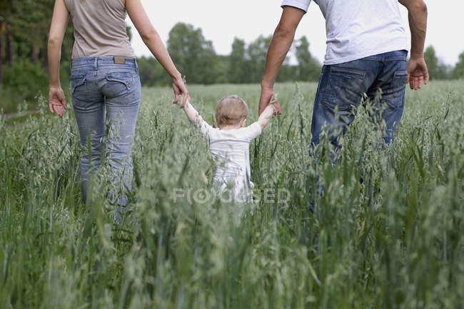 Два родителя, гуляющие в поле с малышом — стоковое фото