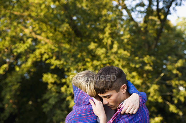 Young couple wrapped in a blanket hugging in park — Stock Photo