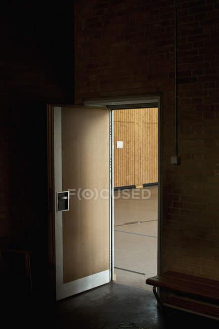 Dunkler Raum mit geöffneter Tür enthüllt Turnhalle — Stockfoto