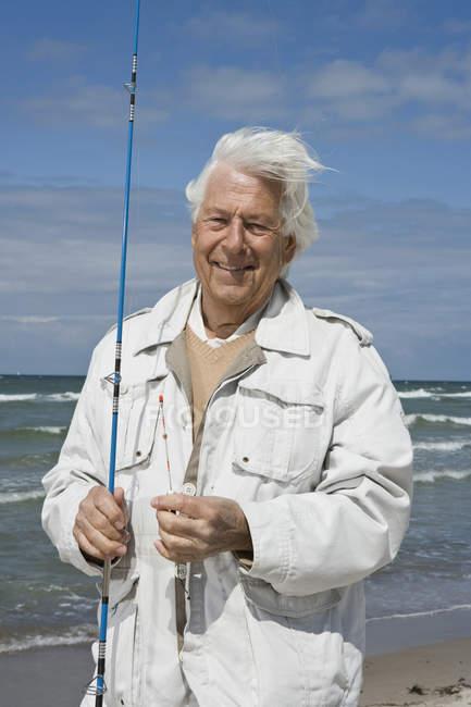 Último homem segurando uma vara de pescar na praia — Fotografia de Stock