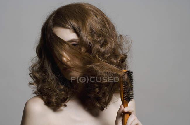 Portrait de jeune femme, tirer les cheveux sur le visage avec brosse — Photo de stock