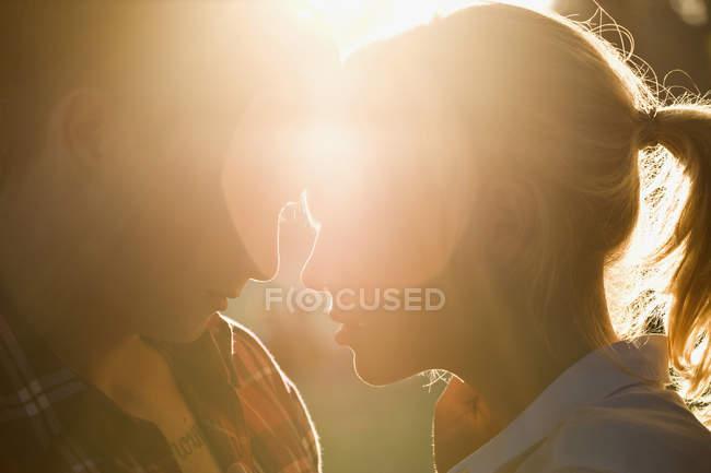 Primo piano di appassionato giovane coppia faccia a faccia in retroilluminazione — Foto stock