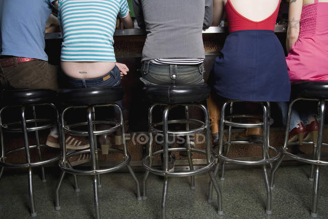 Rear view of row of friends sitting at bar counter — Stock Photo
