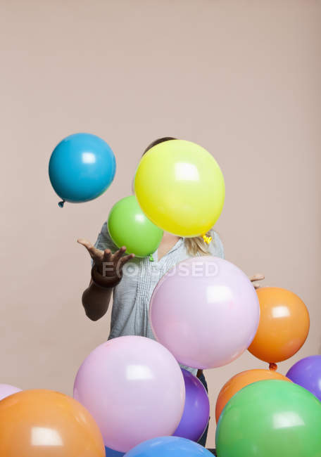 Anonymous woman playing with balloons over pink background — Stock Photo