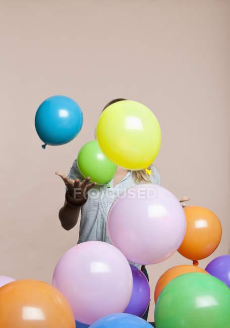 Анонімні жінка грати з кулі над рожевий фон — стокове фото