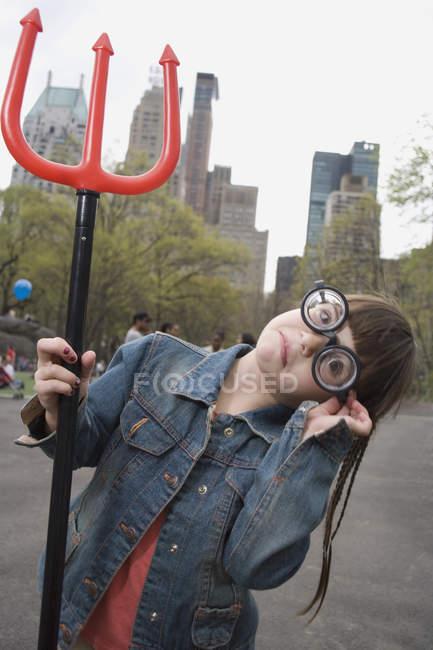 Une jeune fille portant des lunettes drôles et tenant une fourche du diable — Photo de stock