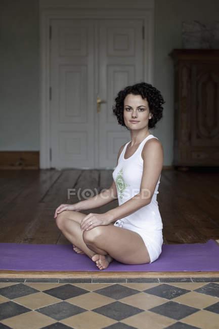 Frau sitzt im Schneidersitz auf Yogamatte und blickt in Kamera — Stockfoto