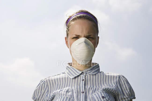 Eine junge Frau mit einer Verschmutzungsmaske — Stockfoto