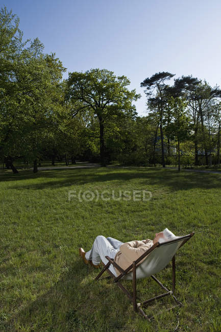 Senior man reclining in a lounge chair on a lawn — Stock Photo