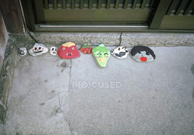Visages drôles peints sur des pierres par étape de porte — Photo de stock
