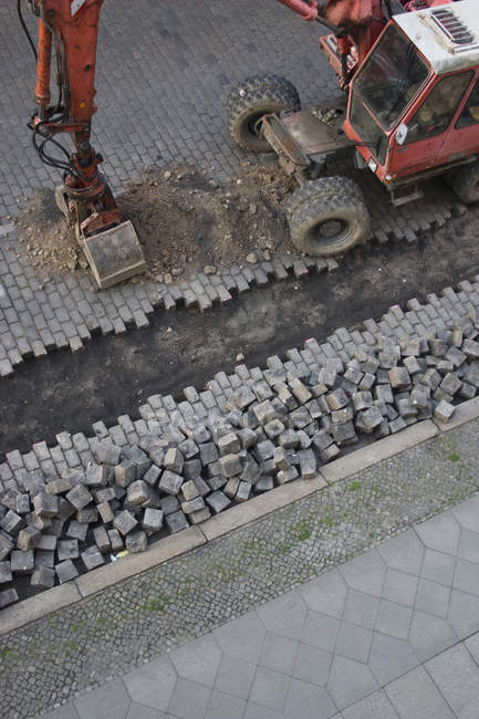 Cropped image of earth digger excavating of cobblestone street — Stock Photo