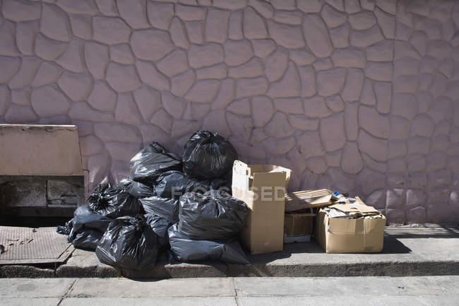 Boîtes et sacs de détritus sur le trottoir — Photo de stock