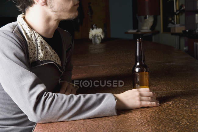 Людини, що сидить у барі з пляшкою пива — стокове фото