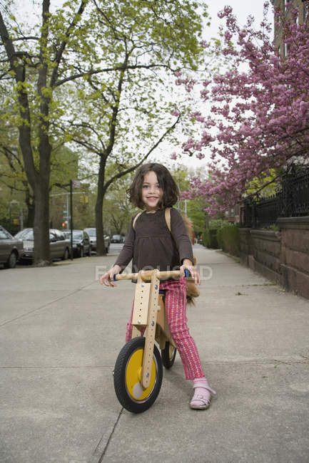 A young girl on a wooden scooter — Stock Photo