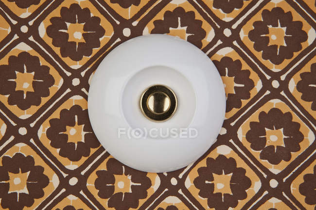 Close up view of vintage doorbell on patterned background — Stock Photo