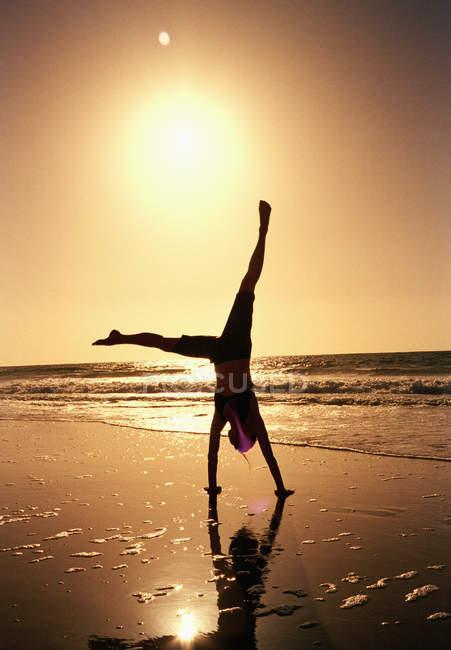 Silueta de mujer haciendo voltereta al atardecer playa - foto de stock