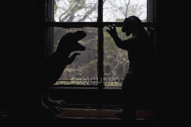 Silhouette zweier Dinosaurierfiguren vor dem Fenster — Stockfoto