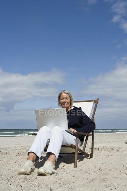 Mulher sênior, sentado em uma espreguiçadeira na praia e usando o laptop — Fotografia de Stock