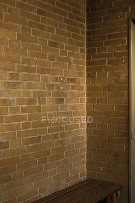 Кирпичный угол и коричневая скамейка — стоковое фото