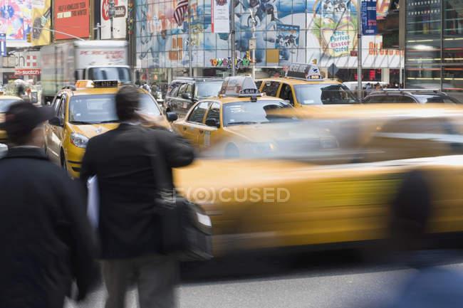 Taxis jaunes et piétons dans la rue de la ville — Photo de stock