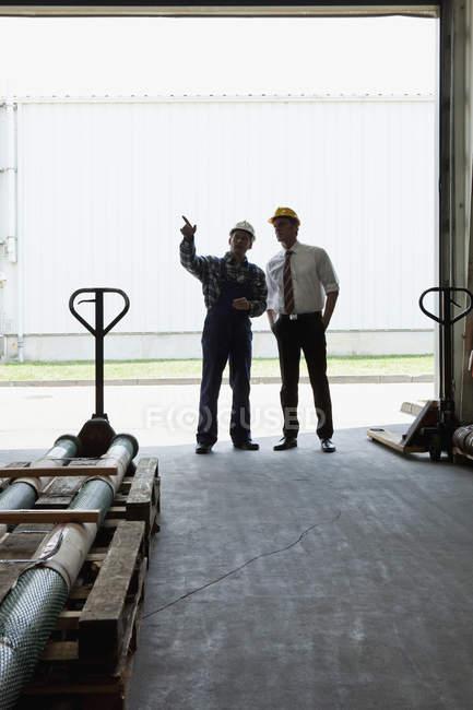 Manager im Gespräch mit einem Arbeiter in einer Lagertür — Stockfoto