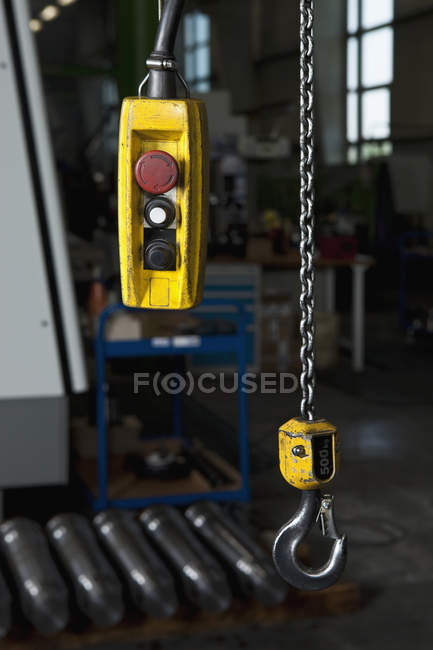 Chain hoist and control at metal parts factory — Stock Photo