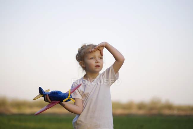 Um retrato de uma jovem segurando um avião de brinquedo e protegendo os olhos, ao ar livre — Fotografia de Stock