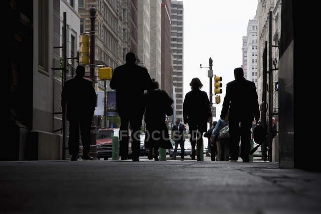 Siluetas de los peatones caminando en arcade, - foto de stock