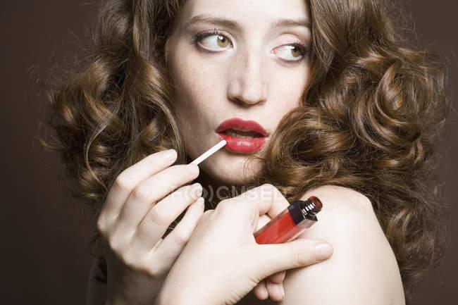 Портрет молодой женщины с блеском для губ — стоковое фото