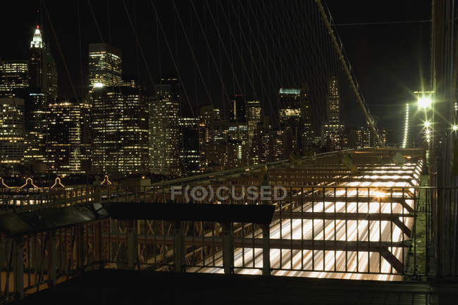 Vista desde el puente de Brooklyn hasta el horizonte de Manhattan por la noche - foto de stock