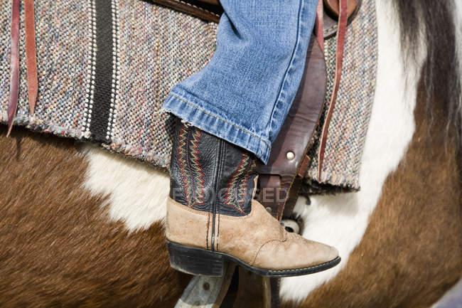 Colheita cowboy perna a cavalo equitação — Fotografia de Stock