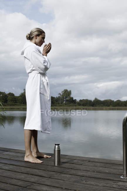 Женщина в Халат, стоящий на пристани спа — стоковое фото