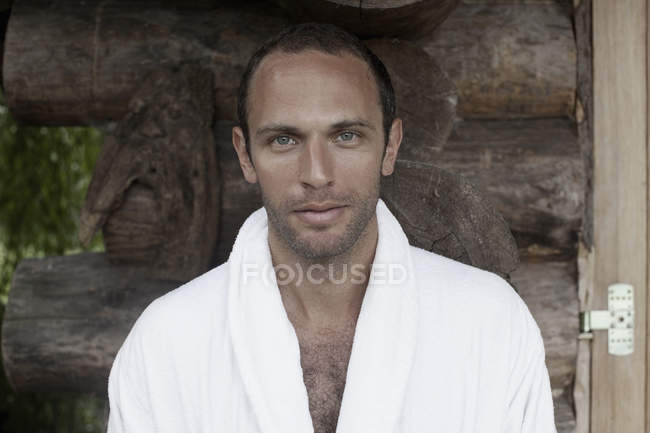 Portrait of man in white bathrobe in wooden background — Stock Photo