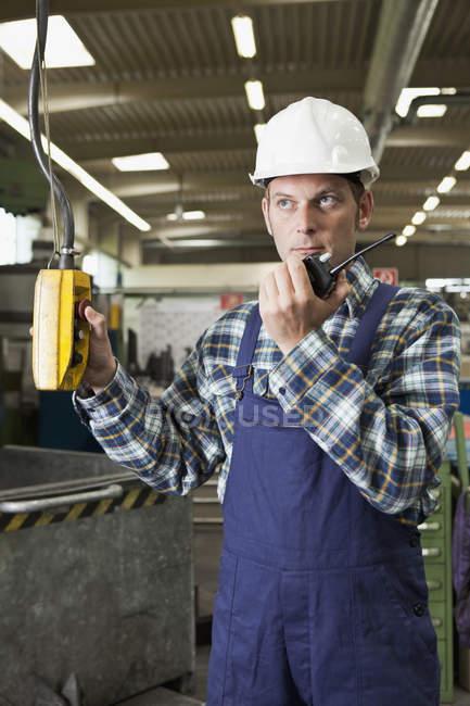 Fabrikarbeiter mit Walkie-Talkie und Bedienung einer Fabrikmaschine — Stockfoto