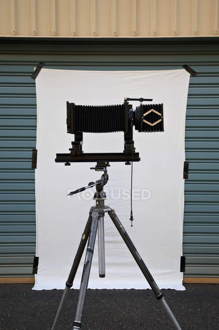 Side view of old-fashioned camera on tripod on back drop set up for photo shoot — Stock Photo